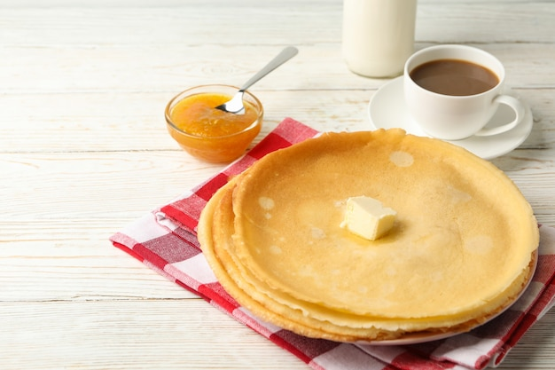 Concept of tasty breakfast with thin pancakes on white wooden table