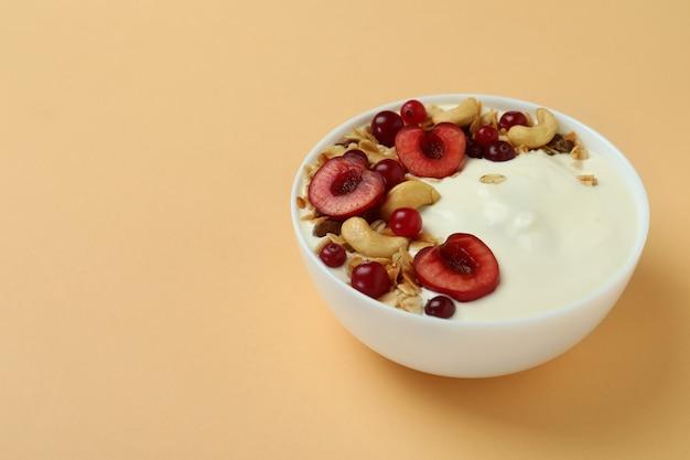Concept of tasty breakfast with yogurt on beige background