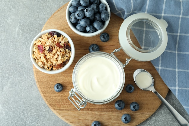 Concept of tasty breakfast with yogurt on gray textured table
