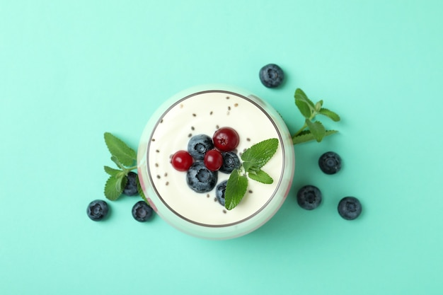 Concept of tasty breakfast with yogurt on mint background