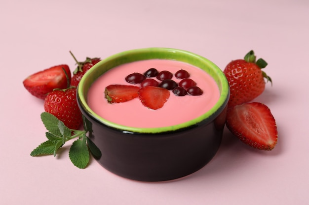 Concept of tasty breakfast with yogurt on pink background