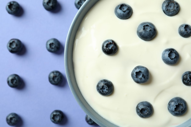 Concept of tasty breakfast with yogurt on violet background