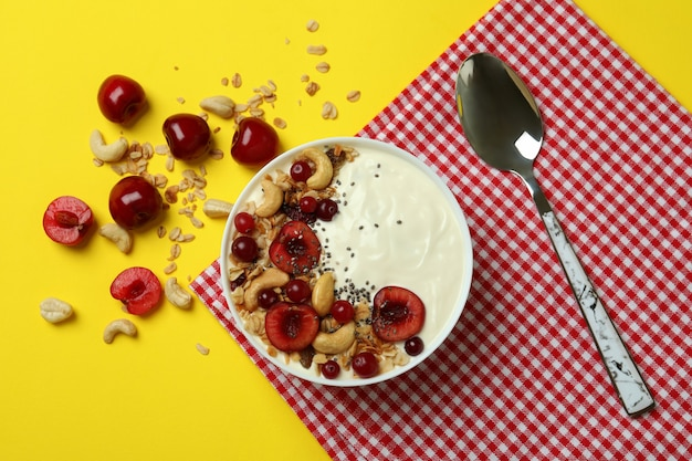 Concept of tasty breakfast with yogurt on yellow background