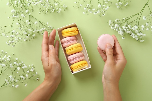 Concept of tasty dessert with macaroons on green background