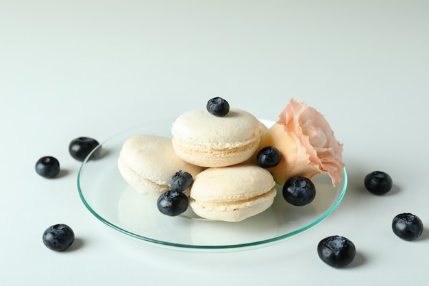 Concept of tasty dessert with macaroons on white background