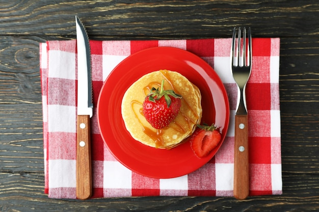 Concept of tasty dessert with pancakes on wooden table