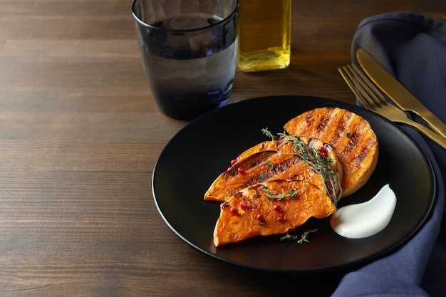 Concept of tasty eating with baked pumpkin on wooden background.