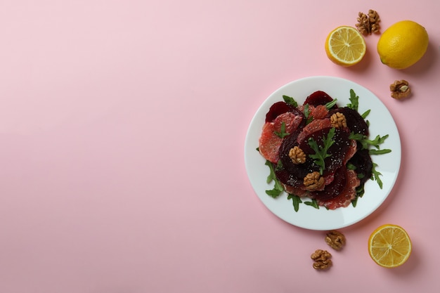 Concept of tasty eating with beet salad on pink table