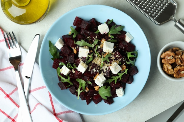 Concept of tasty eating with beet salad on white textured table