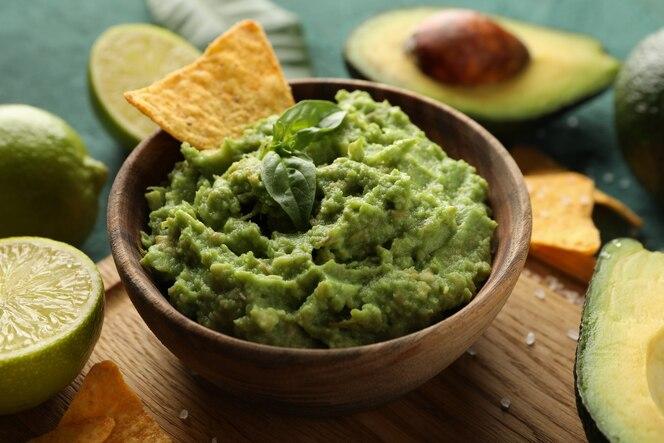 concetto di gustoso mangiare con una ciotola di guacamole su sfondo verde con texture