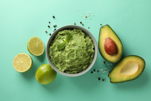 Concept of tasty eating with bowl of guacamole on mint background