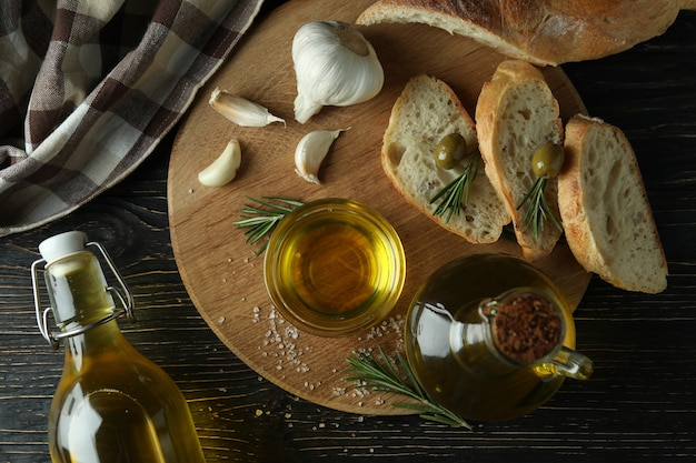 Concept of tasty eating with bowl of olive oil on wooden table