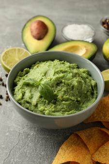 concetto di gustoso mangiare con guacamole e ingredienti su sfondo grigio