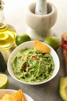Concept of tasty eating with guacamole and ingredients on gray background