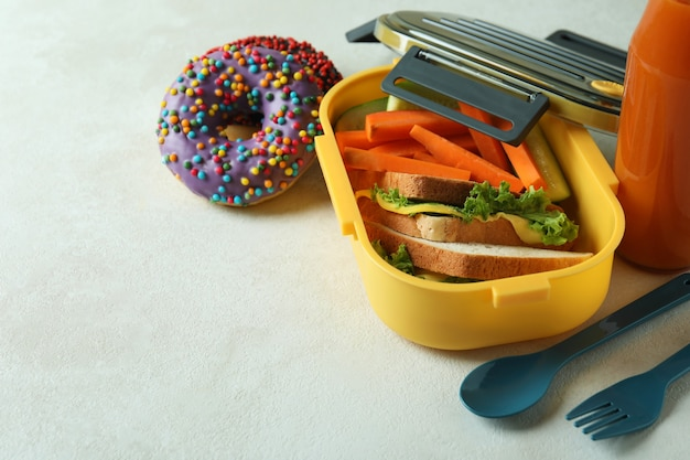 Concept of tasty eating with lunch box on white textured table