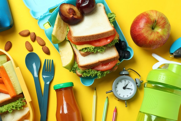 Concept of tasty eating with lunch boxes on yellow background