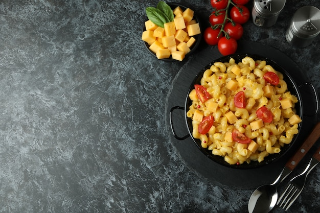 Concept of tasty eating with macaroni with cheese on black smokey table