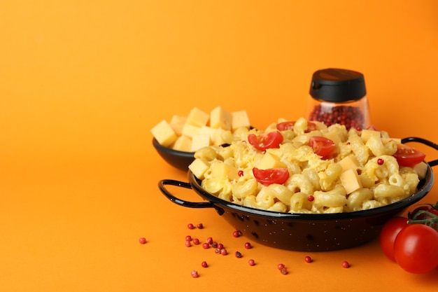 Concept of tasty eating with macaroni with cheese on orange background
