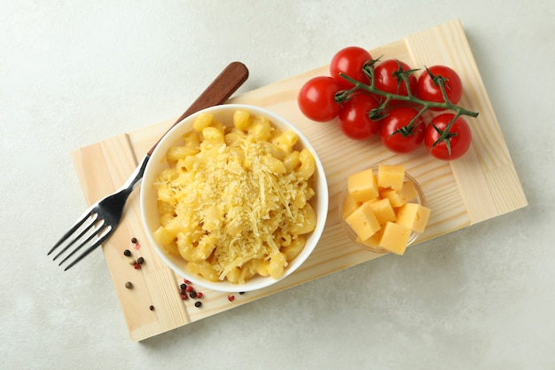 Concept of tasty eating with macaroni with cheese on white textured table
