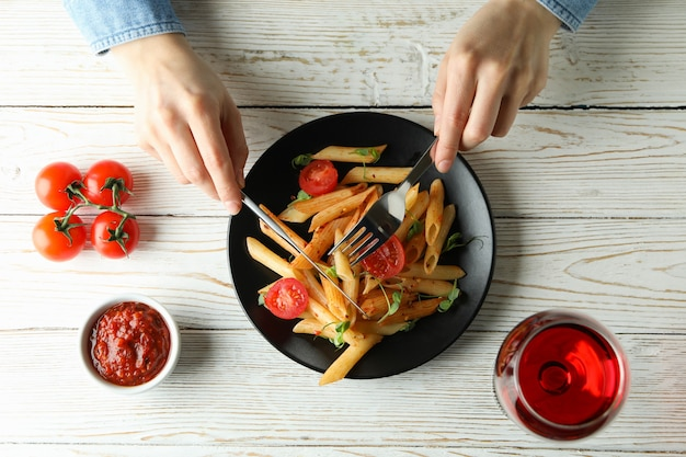Concept of tasty eating with woman eats pasta with tomato sauce, top view