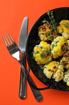 Concept of tasty food with baked cauliflower on orange background.
