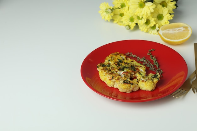 Concept of tasty food with baked cauliflower on white background..