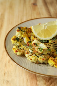 Concept of tasty food with baked cauliflower on wooden background.