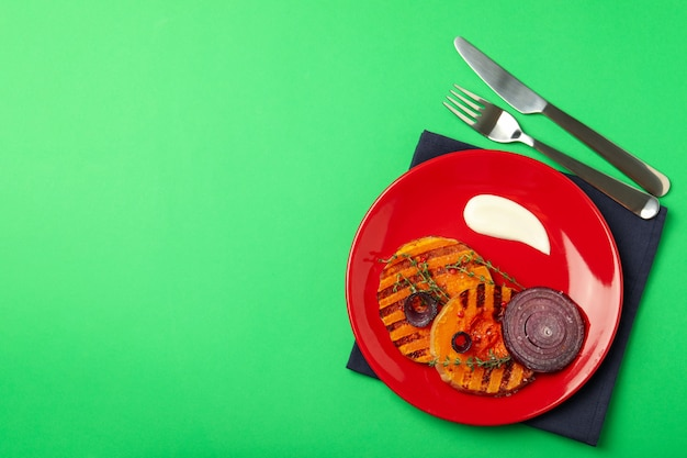 Concept of tasty food with baked pumpkin on green background.