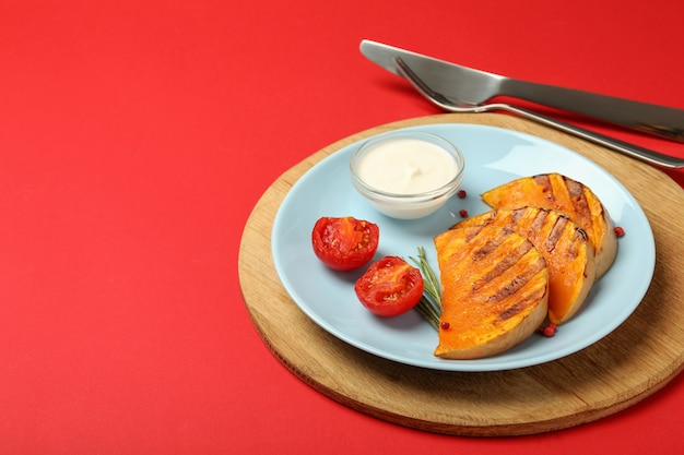Concept of tasty food with baked pumpkin on red background.