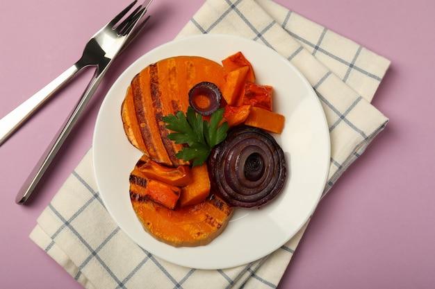 Concept of tasty food with baked pumpkin on violet background.