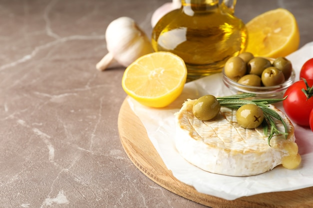 Concept of tasty food with grilled camembert on gray texture table.