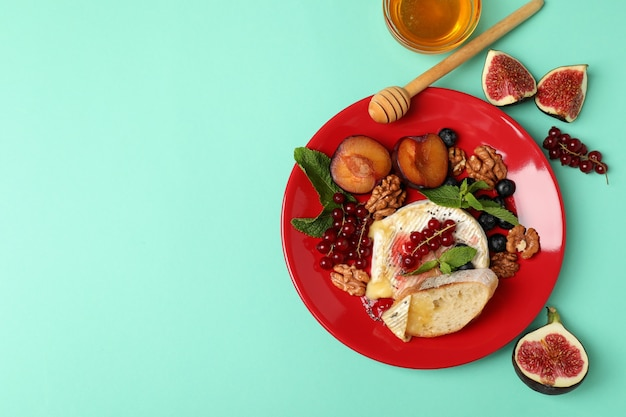 Concept of tasty food with grilled camembert on mint background.