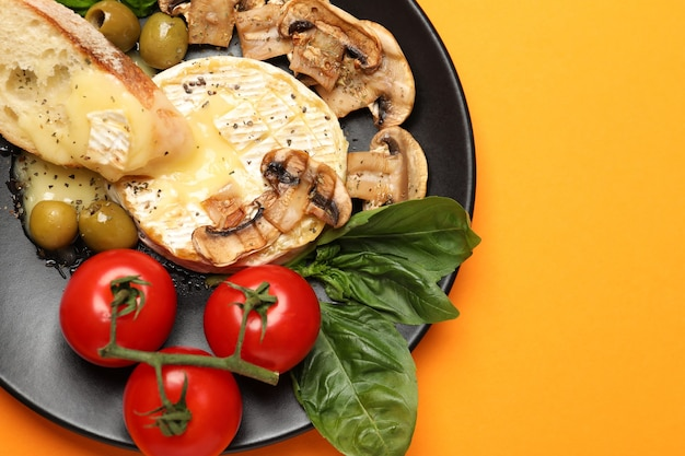 Concept of tasty food with grilled camembert on orange background.