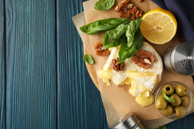 Concept of tasty food with grilled camembert on wooden background.