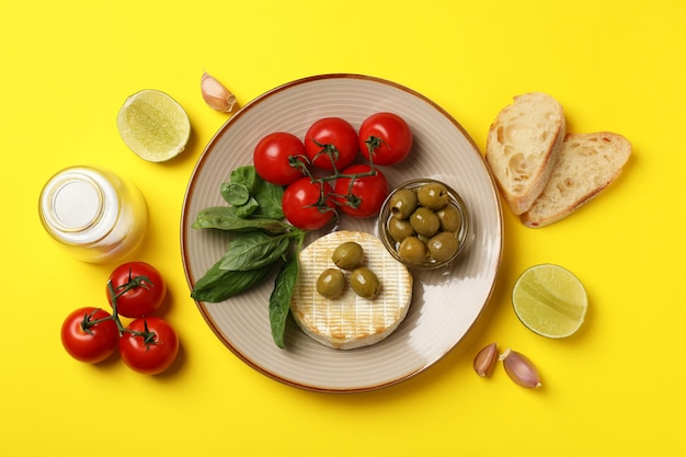 Concept of tasty food with grilled camembert on yellow background.