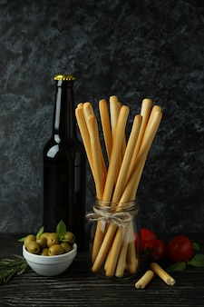 Concept of tasty food with grissini breadsticks on wooden table