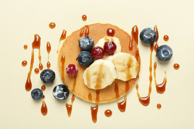 Concept of tasty food with pancake on beige background