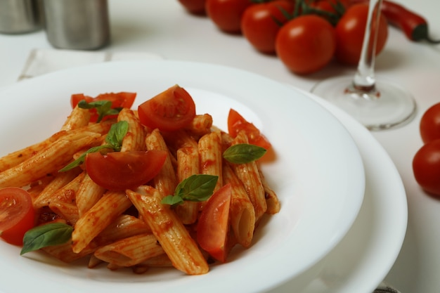 Concept of tasty food with pasta with tomato sauce on white background