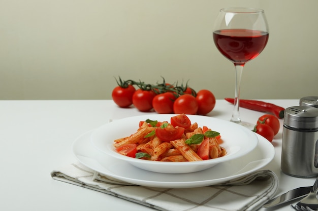 Concept of tasty food with pasta with tomato sauce on white table