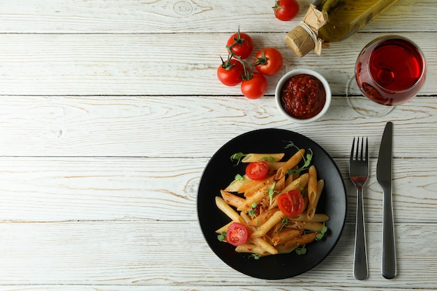 Concept of tasty food with pasta with tomato sauce on white wooden table