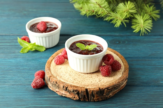 Concept of tasty food with raspberry jam on wooden background