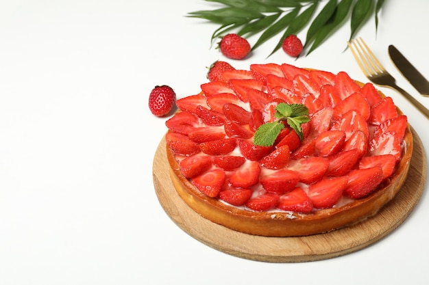 Concept of tasty food with strawberry tart on white background.