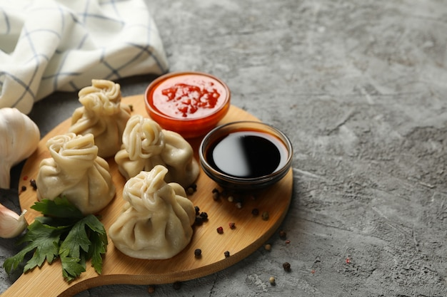 Concept of tasty lunch with board of khinkali on gray background