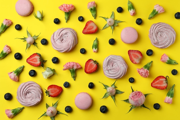 Concept of tasty macaroons and marshmallows on yellow background