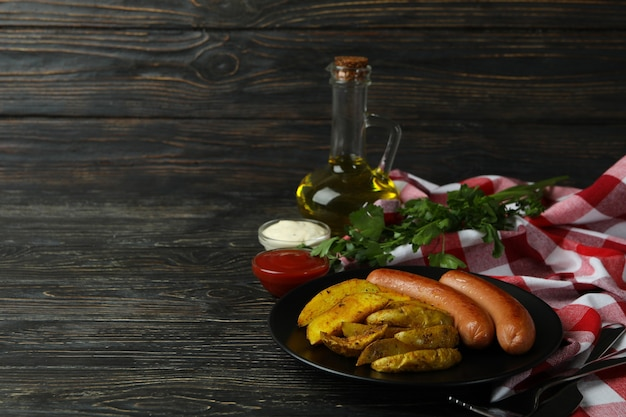 Concept of tasty meal with potato wedges on wooden