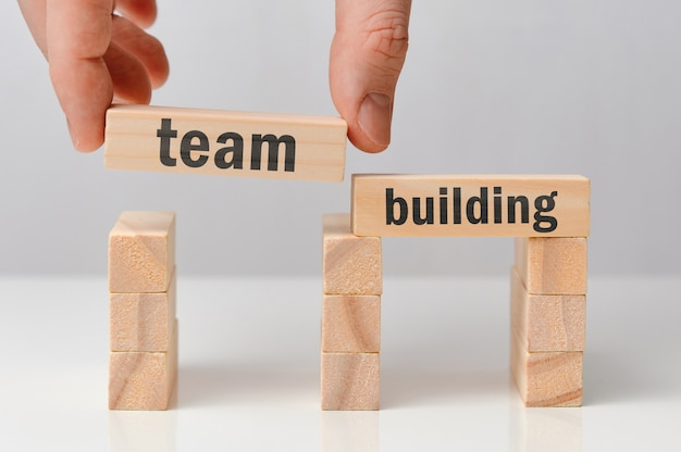 Concept of team building - hand holds a wooden block with the inscription.