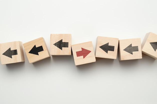 Concept of think differently - wooden cubes with arrows.