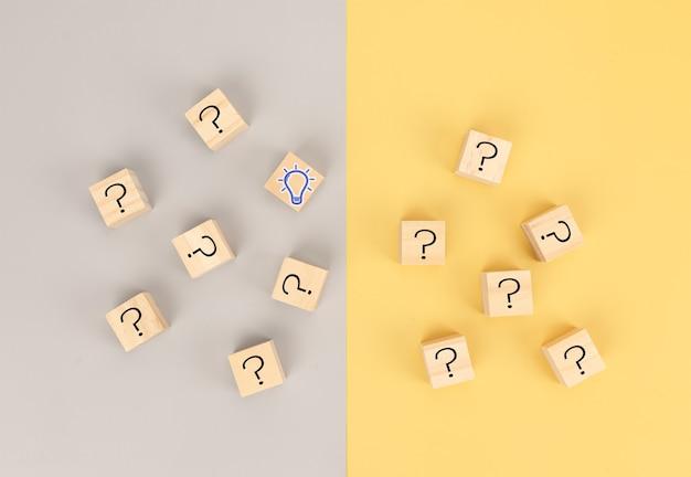 비즈니스를 위한 문제 해결에서 아이디어를 찾는 개념입니다. 나무 큐브 물음표와 전구 아이콘