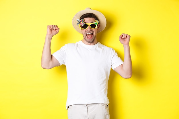 Concept of tourism and lifestyle. happy man winning trip to resort, shouting yes and raising hands up, triumphing, wearing sunglasses and summer hat, yellow background.