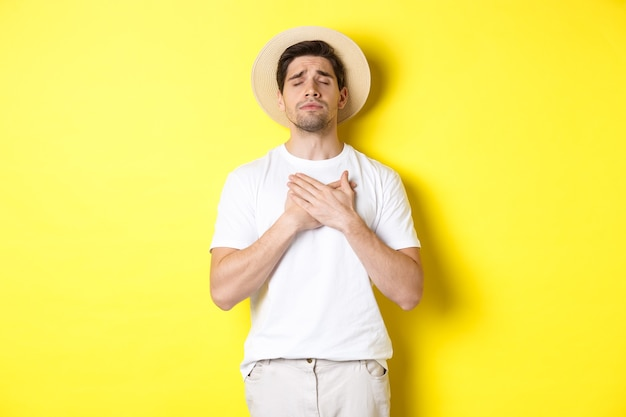 Concetto di turismo ed estate. uomo romantico con cappello di paglia dall'aspetto nostalgico, chiudere gli occhi e tenersi per mano sul cuore, in piedi su sfondo giallo.